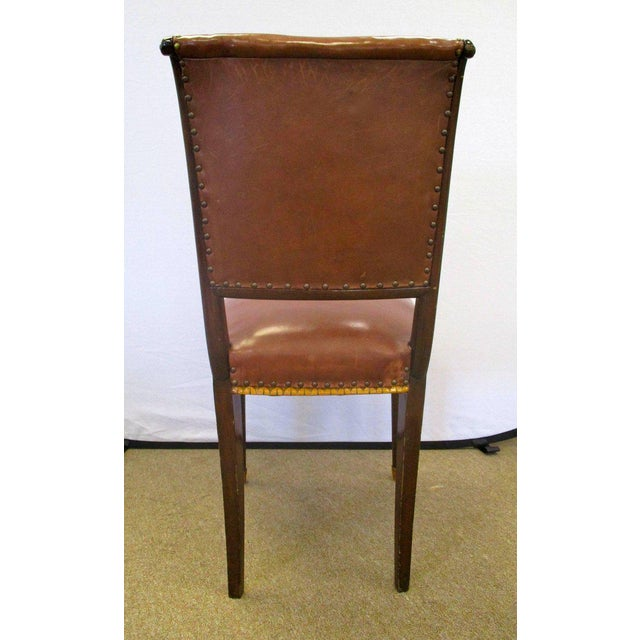 Set of four French Art Deco chairs with carved detail. They are upholstered in a rich brown leather with brass nailheads....