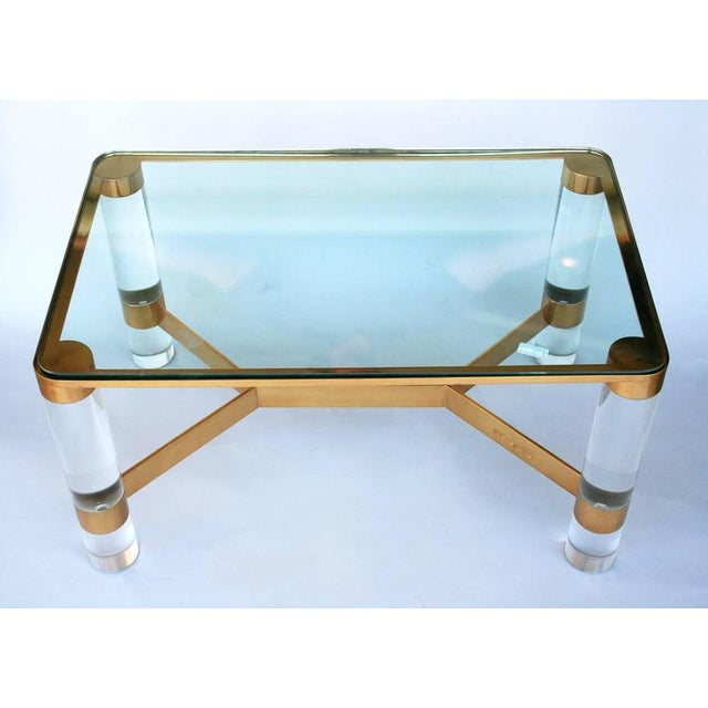 A nice scaled occasional table or small cocktail/coffee table with Lucite legs, brass banding and stretcher with inset...