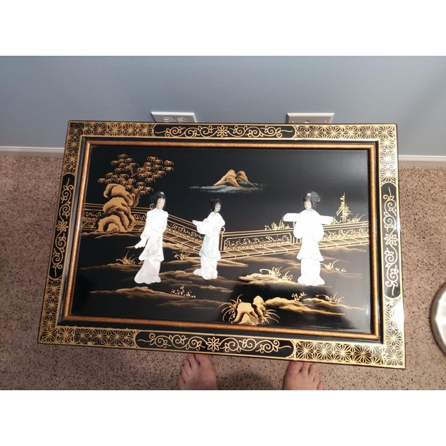 Like new decorative Asian chest made of authentic black lacquer with real inlaid mother of pearl figures. Doors open to...
