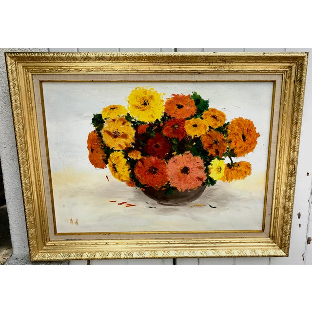 This is a vintage oil painting of yellow, red and orange flowers set against a white background and presented in a...