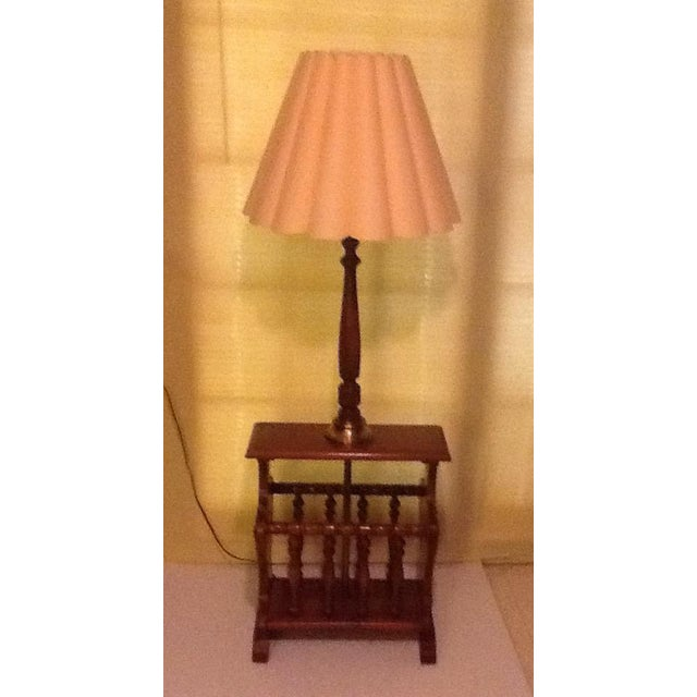 Vintage mid-century wood and brass side table, magazine rack, lamp combination. With a pink colored shade. Shade is in...
