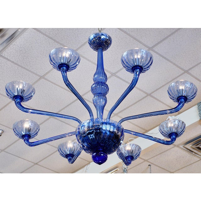 Blue Murano glass chandelier featuring 10 branches, large bobeches, and a blown glass stem