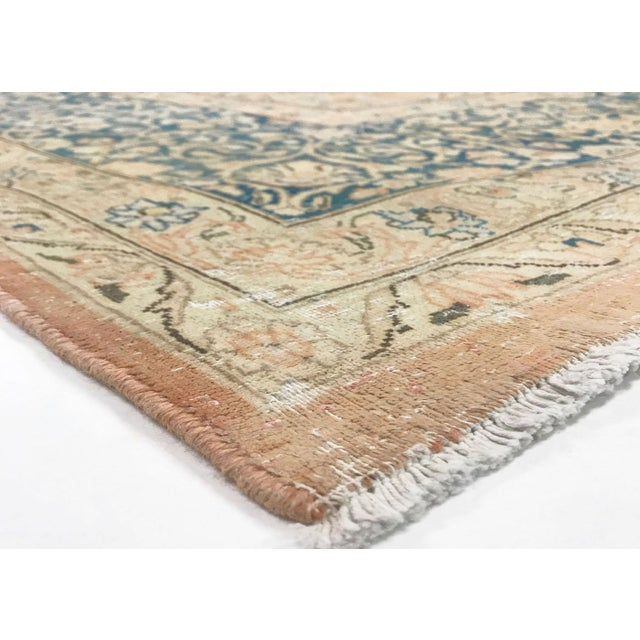 This vintage, distressed Persian rug was hand woven in Iran in the mid 1960's. The colors and pattern have been hand...