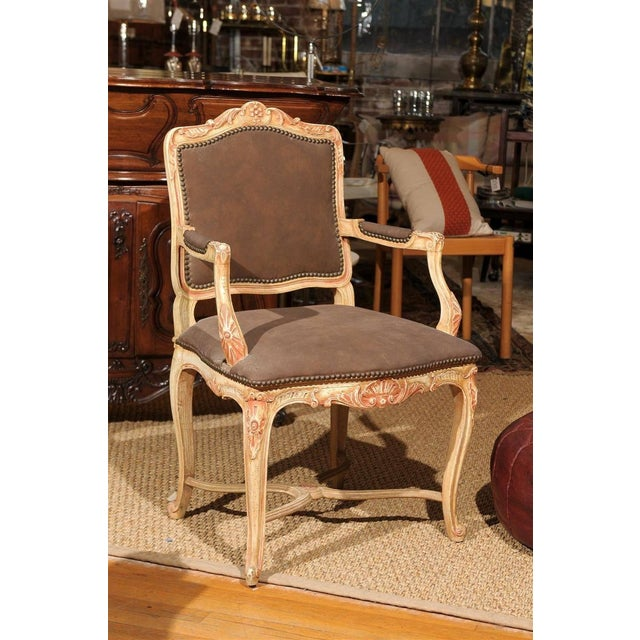 20th Century hand carved and painted wooden bergere chair in the Louis XV style with the seat, back, and arms upholstered...
