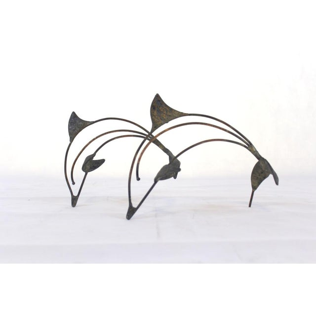 A Mid Century hammered copper sculpture of a pair of dolphins welded together in mid leap. A simple and elegant accessory...
