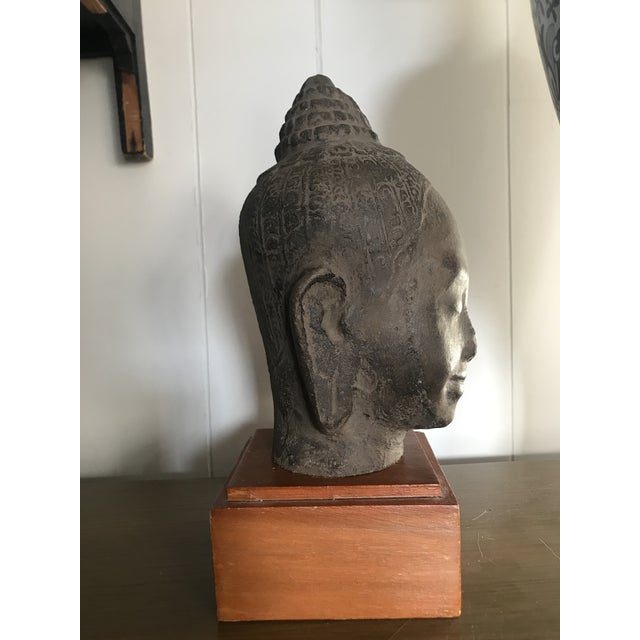 "This is an antique Cambodian Buddha head with 10"" wooden base. The piece is from the early 20th century."