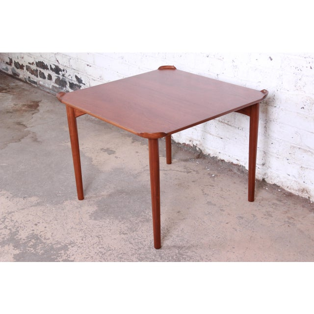 A handsome teak game table designed by Danish architect Finn Juhl for Baker Furniture. The table features stunning teak...
