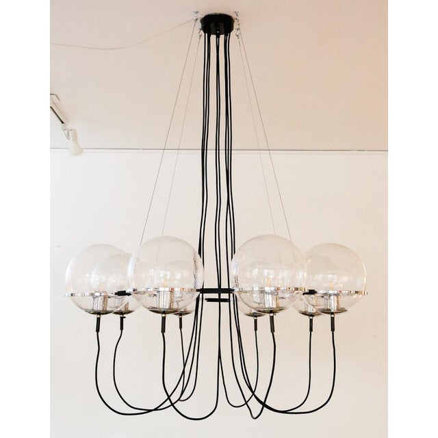 Extra large version of the 'Saturnus' chandelier by RAAK of the Netherlands. Eight blown glass globe shades with tiny air...