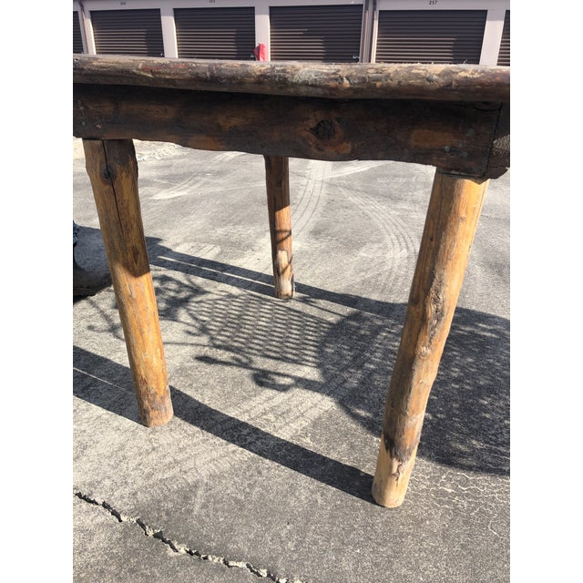 A very rustic almost square hand made Adirondack style side table, work table or kitchen island having rough hewn tree...