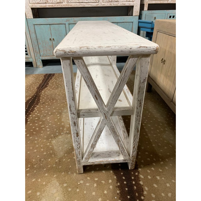 Distressed white shelving unit with two levels and beautiful design. This piece features a beautiful spackle white finish...