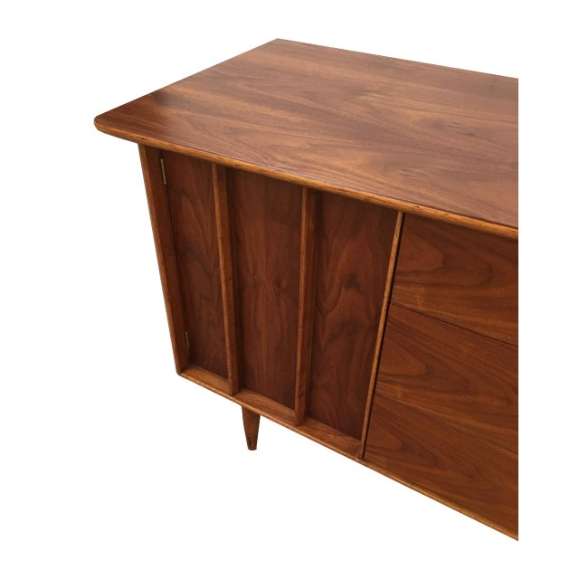 Beautiful walnut credenza from Kent Coffey. Features an angled top with gorgeous graining. Two doors on either side that...