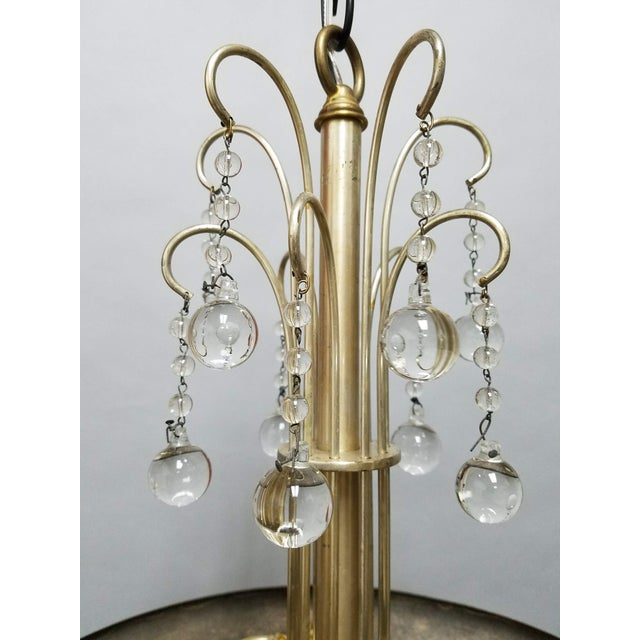 Simple but elegant brass plated dish fixture with a waterfall of crystal balls from the top. There is some wear to the...