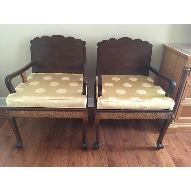 A pair of 1970's custom hand carved arm chairs with claw feet and yellow cushions. The carving is on the back of the chair...