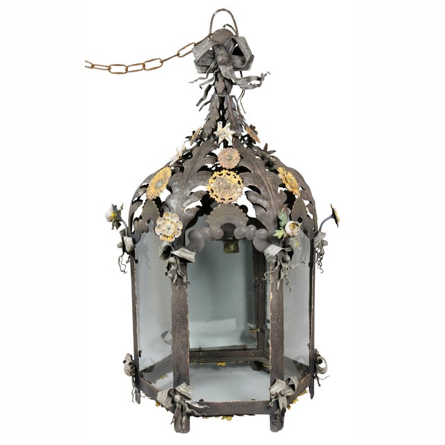 Domed top with leaf decoration and flower heads, cylindrical body with glass panels.