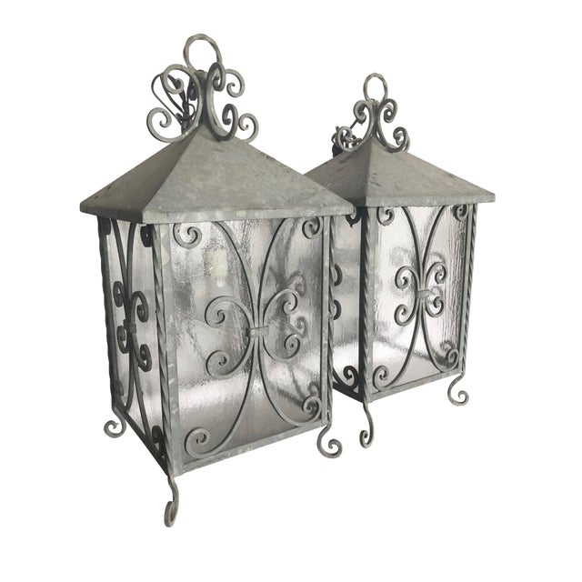 A pair of 1950s Italian galvanized steel lanterns suitable for indoor or outdoor use. Lanterns have hand wrought scrolling...