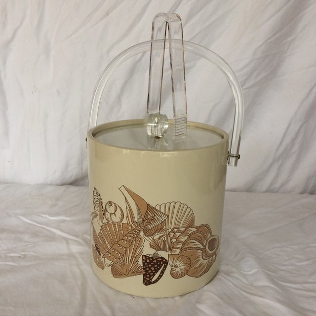 This ice bucket has a beach theme with various seashells on vinyl. The top is Lucite with a Lucite round knob. It comes...