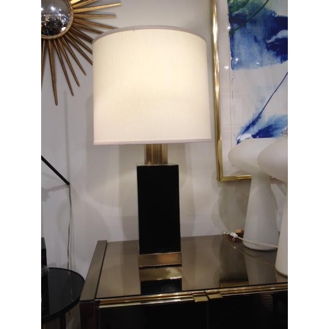 This lamp is vintage and has a black ceramic body with brass accents. It has modern aesthetic with a new lamp shade. We...