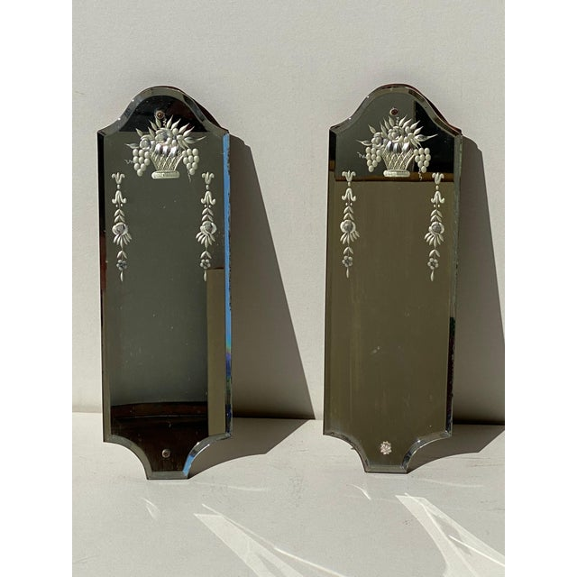 A matching pair of Venetian mirrors with etched flower baskets and swags. They have beveled edges and scalloped corners....