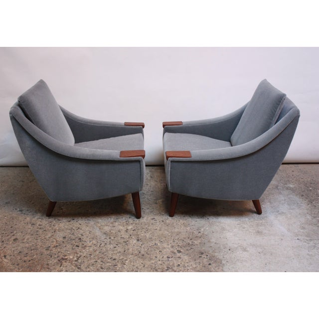 Pair of 1960s Danish lounge chairs newly upholstered in a powder blue mohair with teak armrests raised on turned teak...