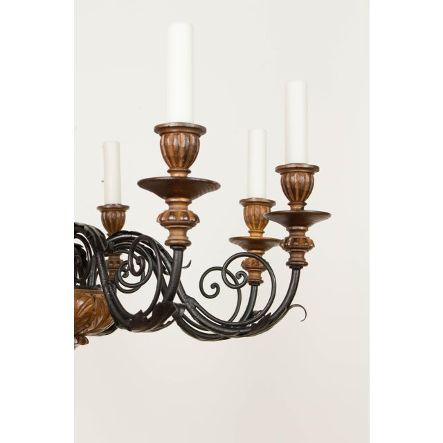 Iron and wood eight arm chandelier. Carved Wood, with wrought iron arms. Carvings of pineapple and leaves. Beautifully...