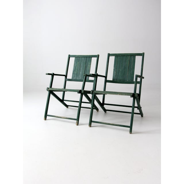 A pair of vintage slat wood folding chairs circa the 1950s. The outdoor wooden chairs feature slat seats and backs with a...