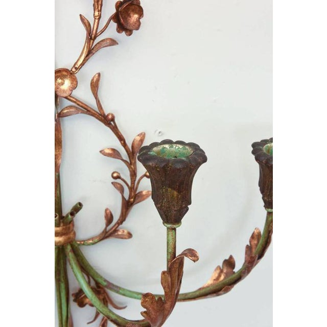 Pair of sconces, painted and parcel-gilt iron, with each backplate formed as an arrow, embellished by curling vines,...