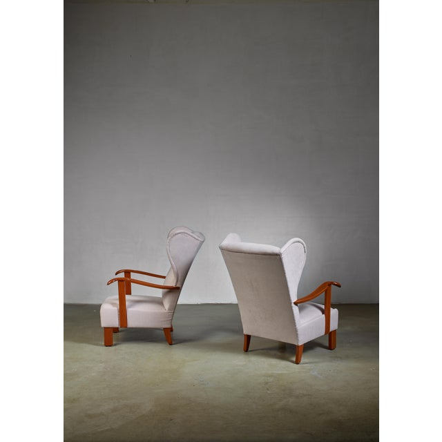A pair of model '1582' Fritz Hansen lounge chairs with expressive wings and curved armrests. The chairs have been newly...
