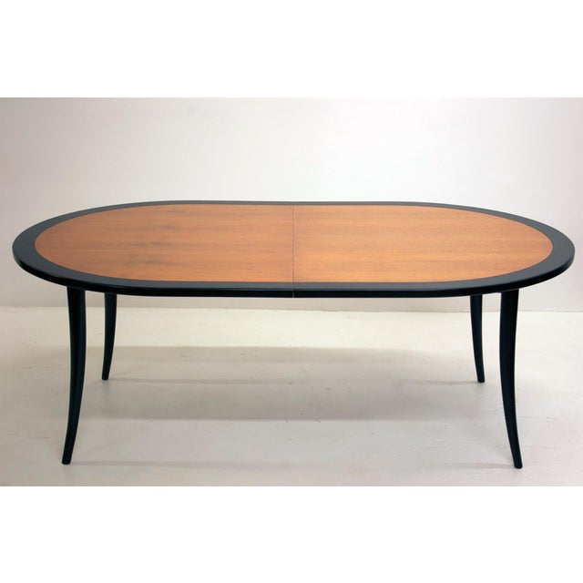 An elegant ebonized and bleached walnut dining table designed by Harvey Probber, circa 1950. Featuring flared saber legs...
