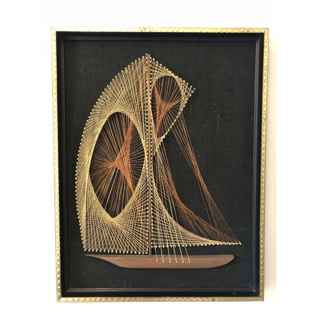 A vintage mid-century modern wire string art of a sailboat. The wire colors used are gold and copper and are attached to a...