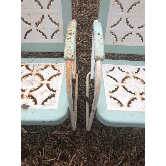 An inviting set of four classic country metal garden arm chairs having cut out charming patterns on the seats and backs....