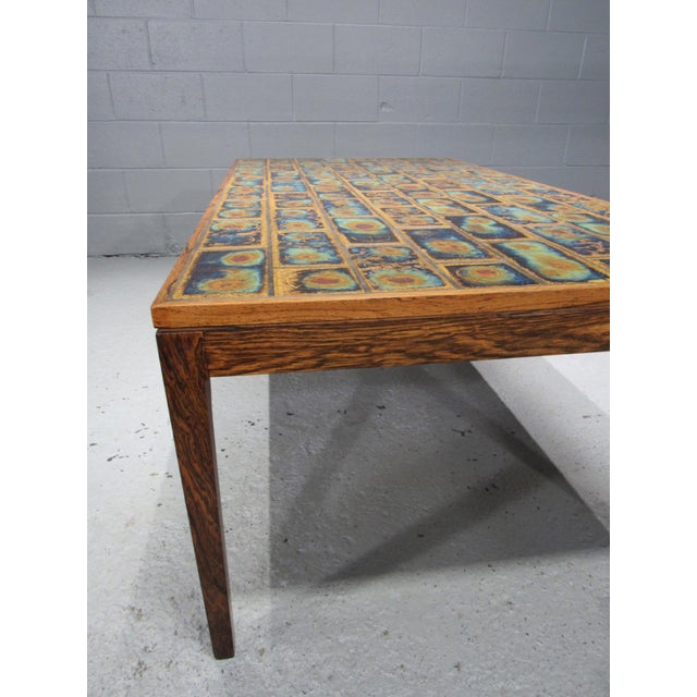Large Danish modern rosewood and tile coffee table. This stunning tile coffee table features beautiful tile work and a...