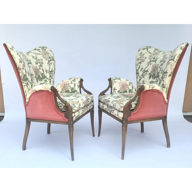 A classic pair of elegant carved French Hollywood Regency Style chairs with a stately butterfly shape back, carved arm and...