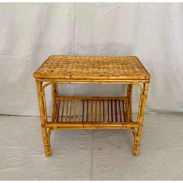 Mid century wicker and rattan side table with pencil reed magazine rack below.