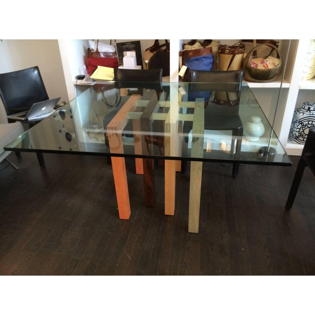 Sculptural table base has four connected solid wood supports in mahogany, cherry, walnut and maple, in a modern asymmetric...