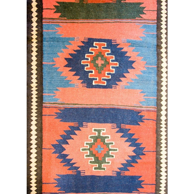 An early 20th century antique Persian Bakhtiari runner with ten diamond medallions woven in crimson, salmon, indigo, and...