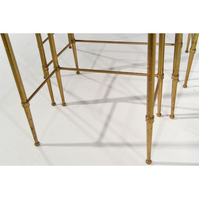 Set of three brass and wood nesting tables. Minuscule loss to veneer with light oxidation to brass. These tables would be...