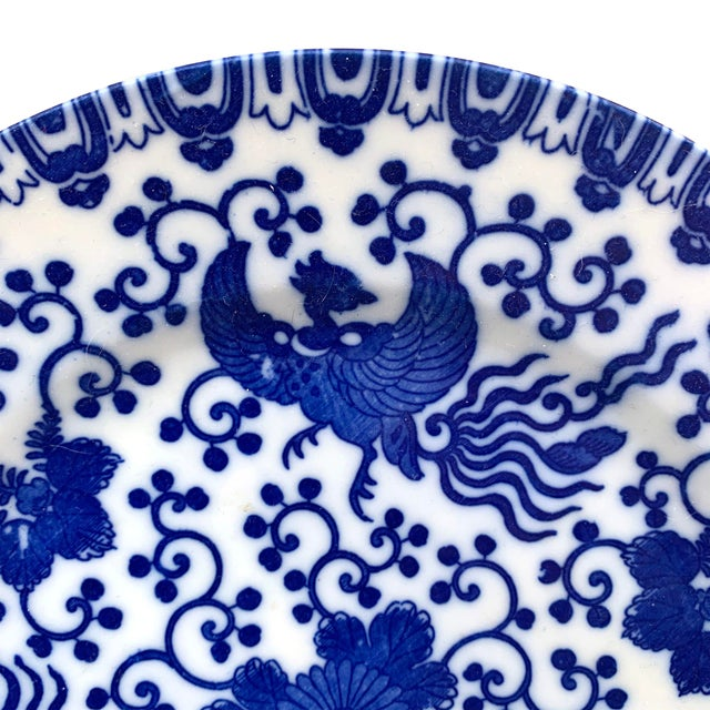 A beautiful early 20th century Japanese blue and white porcelain plate with several phoenix amidst a field of scrolling...