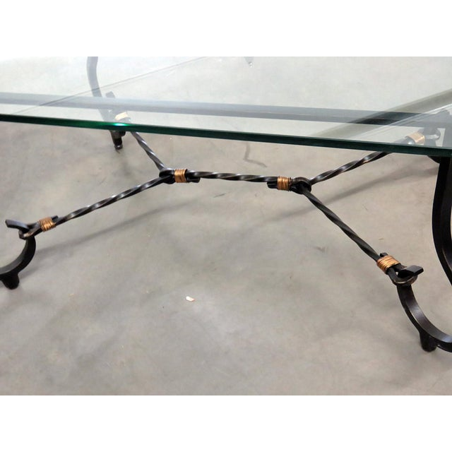 Jansen style glass top coffee table with an iron base.