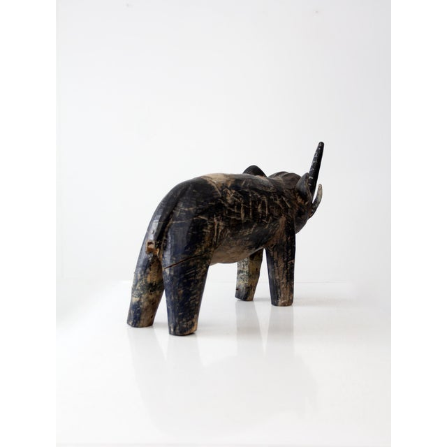 An antique carved wood elephant statue. Beautifully aged, the wooden elephant features navy blue and white painted coloring.