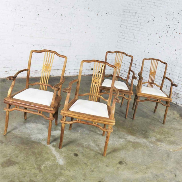 Handsome set of four Indonesian Ming style dining chairs with arms in natural teak and upholstered drop in seats. They are...