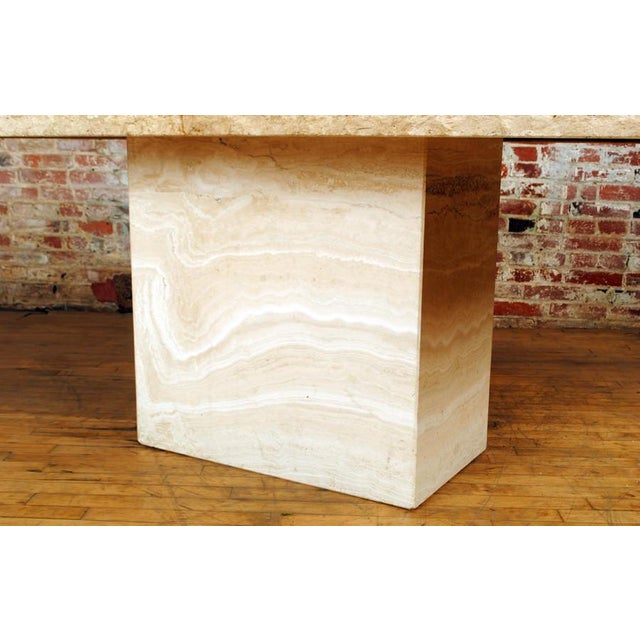 An unusual italian travertine pedestal table with a carved edge, believed to be made by stone international.