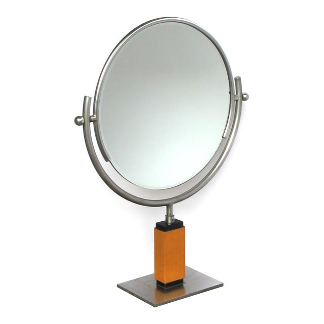 the round beveled mirror within an adjustable steel frame raised on a rectilinear maplewood support; all over a steel base