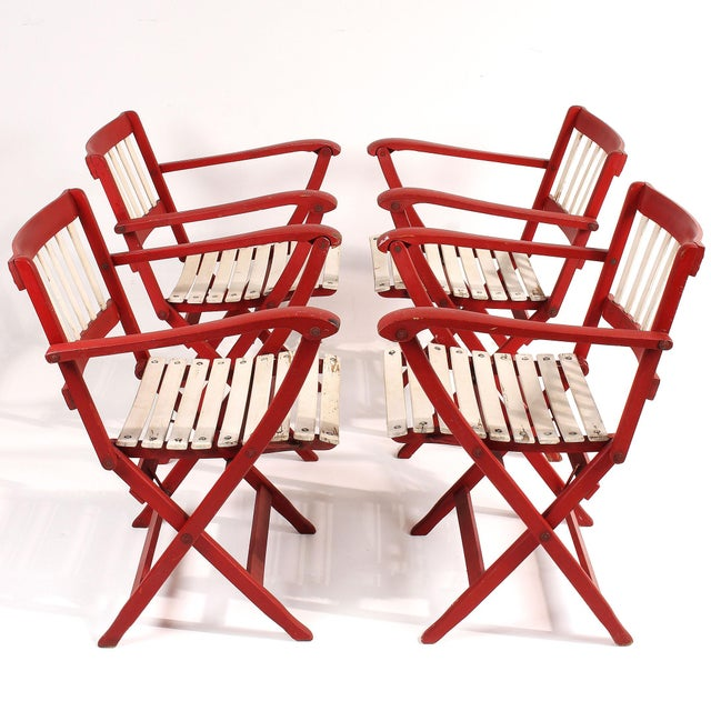 A rare set of four mid-century slatted wood folding deck chairs with armrests made by well-known Italian manufacturer...