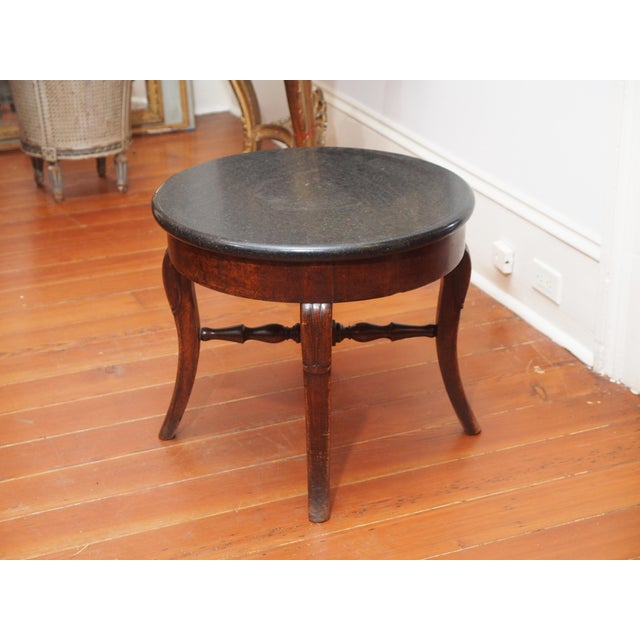 A mid-19th century, Restauration table base with a later polished stone top. The base, with cabriole legs, is joined by a...