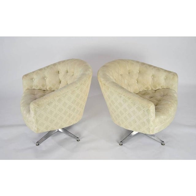 A comfortable pair of Ward Bennett lounge or club chairs with a swivel base and tufted seat and back.
