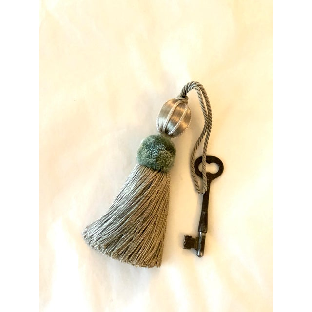 Sage and taupe beaded key tassel w twisted cord that creates the key loop. Light sage colored frosted glass bead separates...