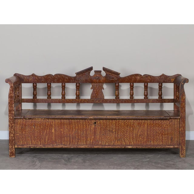 The lovely symmetry and hand painted faux finish on this antique Romanian Hungarian bench circa 1875 remains as handsome...