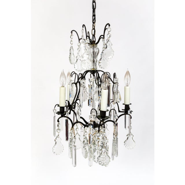 A beautiful pair of black toned bronze, dominative birdcage style chandeliers. They are decked with numerous crystal...