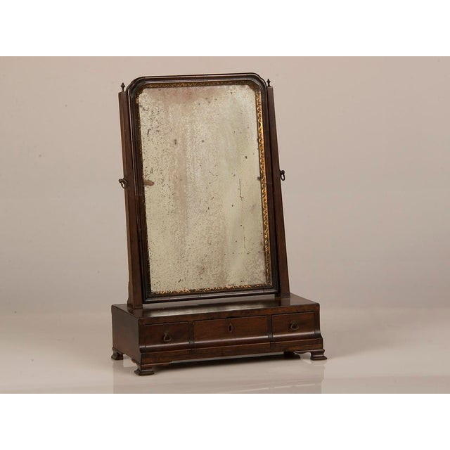 A George III period mahogany dressing mirror from England c. 1790 having a shaped front with three drawers for storage and...