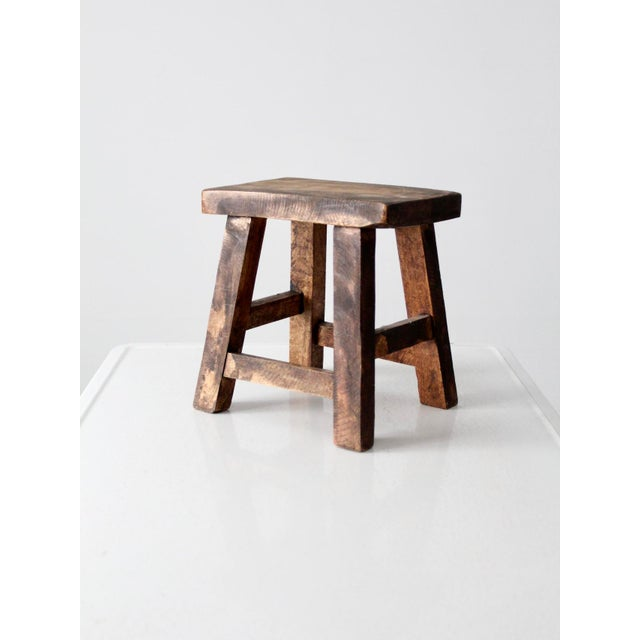 This is a vintage Chinese stool. The small wooden riser features a dark tone stain and clean lines.